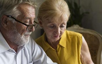 Primer plano de un hombre y una mujer mayores leyendo unos papeles