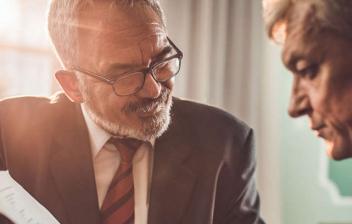 Hombre sonriente mostrando unos papeles a otro hombre mayor
