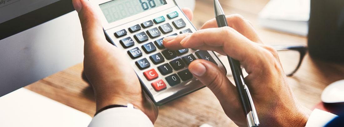 Mano sosteniendo una calculadora y un bolígrafo