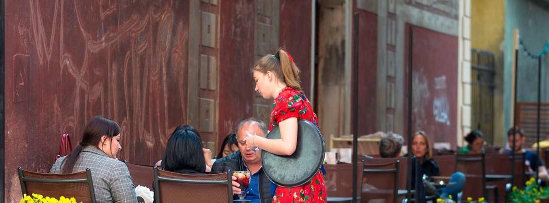 Camarera atendiendo una mesas en una terraza