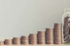 Columnas de monedas en sentido ascendente y un tarro de cristal lleno de monedas