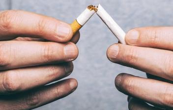 Manos rompiendo un cigarro