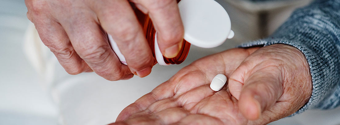Manos de persona mayor con pastillas