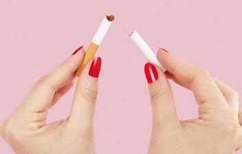 Manos de mujer rompiendo un cigarrillo