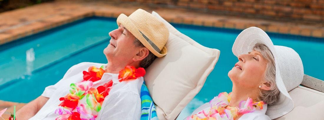 Hombre y mujer mayores sentados en unas hamacas junto a una piscina