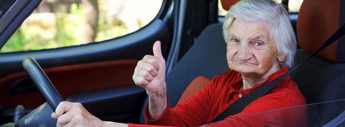 conductora mayor al volante levanta el pulgar