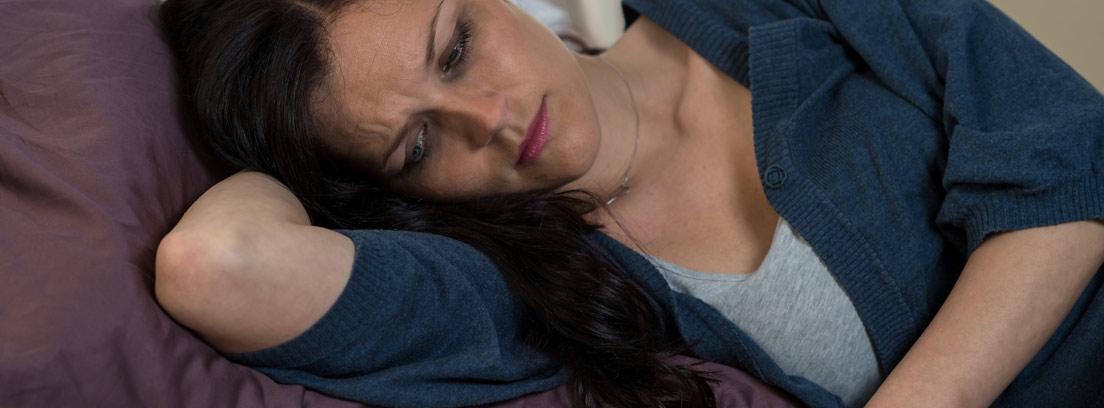 Mujer tumbada en la cama con gesto lloroso mira una foto