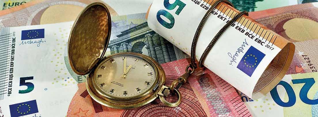 Reloj y billete enrollado sobre billetes de euro