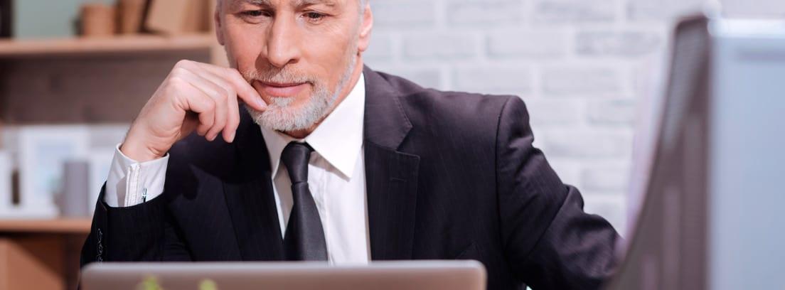 Hombre mayor con traje trabajando frente a un ordenador