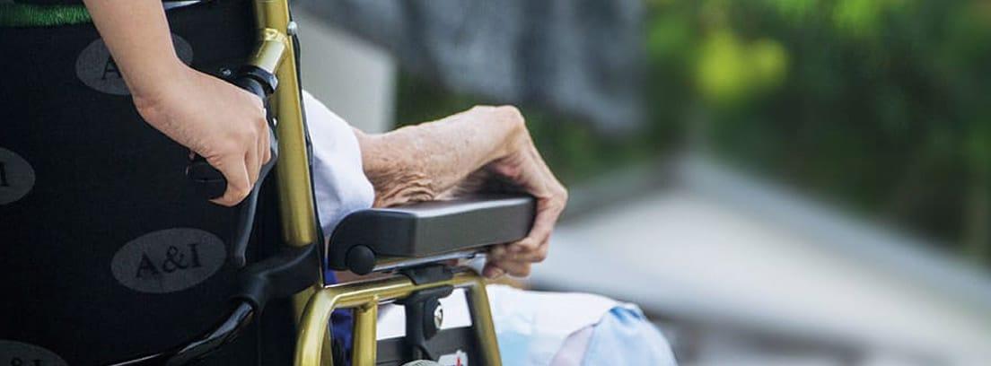 Vista parcial de una silla de ruedas llevando a una persona mayor