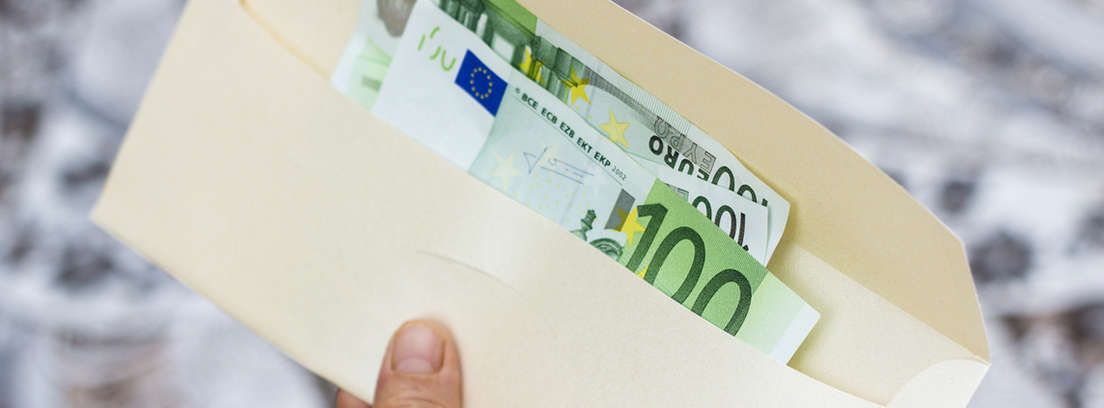 Mano sujetando un sobre con billetes de euro