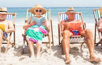 Varias personas mayores sentadas en tumbonas en la playa