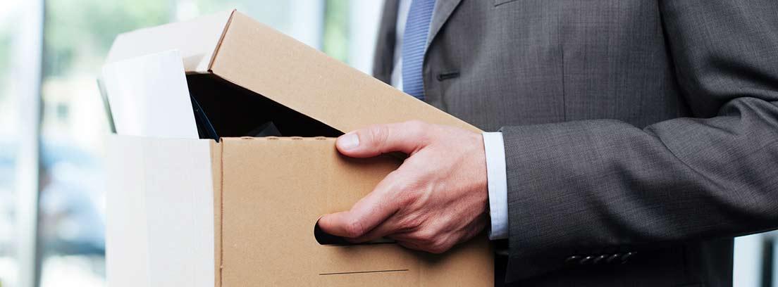 Hombre con traje llevando una caja