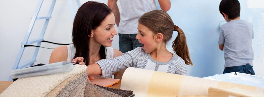 Mujer y niña mirando materiales de reforma y hombre y niño al fondo pintando una pared