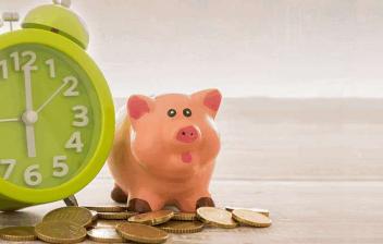 Reloj junto a monedas y una hucha de cerdo