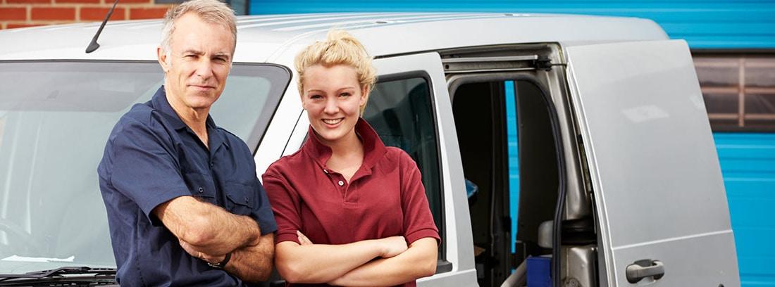 Hombre y mujer apoyados en una furgoneta de una empresa familiar