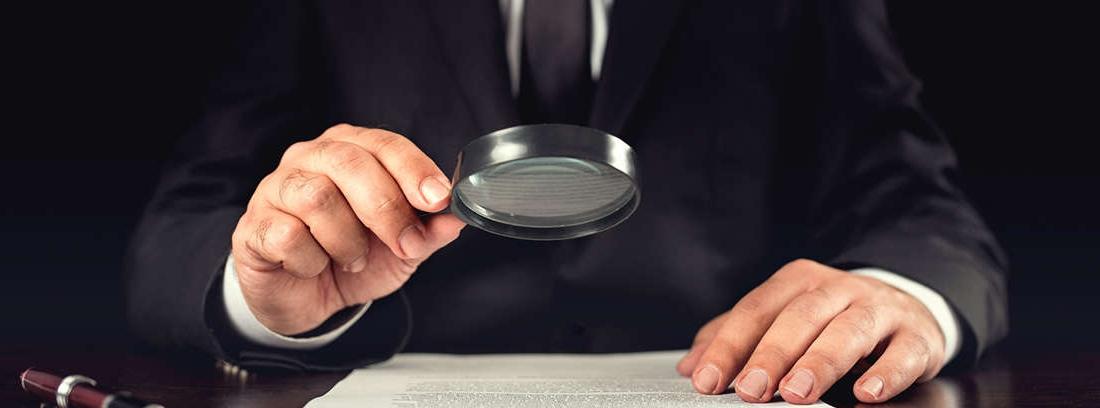 Hombre mirando con una lupa un documento
