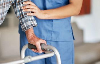 Enfermera y hombre con un andador