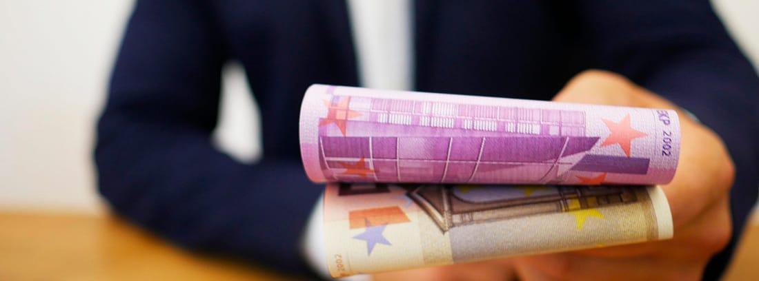 Hombre extendiendo unos billetes de euro