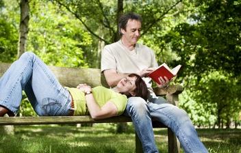 Pareja en un banco leyendo un libro