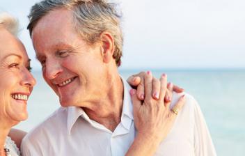 Hombre y mujer mayores en la playa abrazándose y sonriéndose