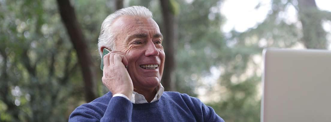 Hombre mayor sonriente usando un ordenador y un teléfono móvil