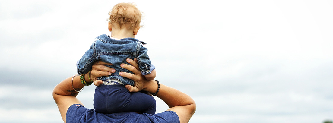Hombre de espaldas con un niño sobre los hombros