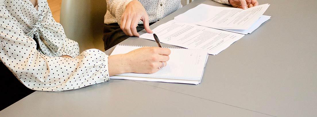 Una mujer escribe en un cuaderno acompañada de otra con documentación
