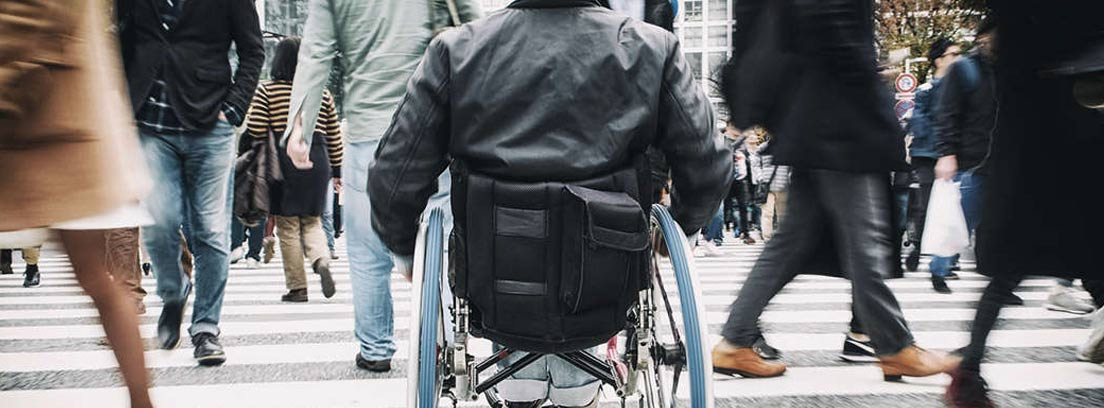 Hombre de espaldas en una silla de ruedas cruzando un paso de peatones