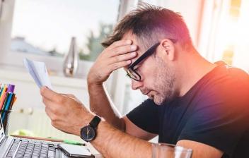 Hombre con gesto preocupado delante del ordenador mirando unos papeles