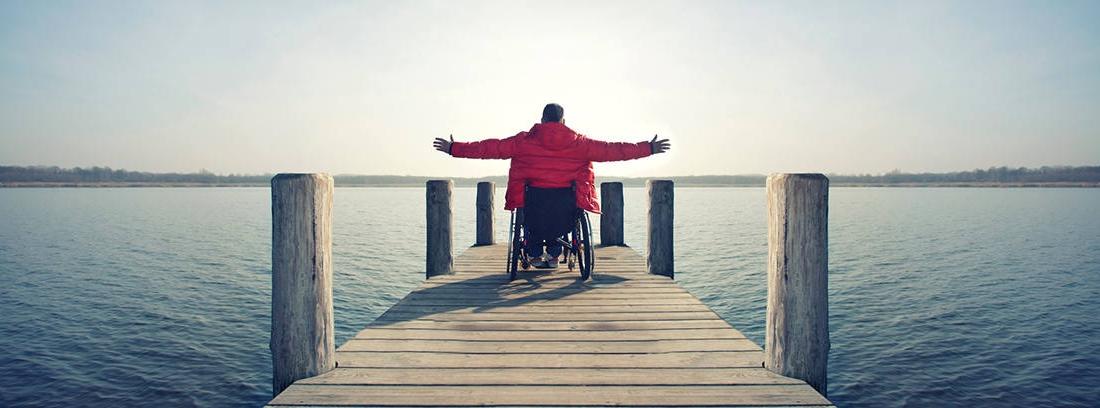 Hombre en silla de ruedas levantando los brazos en un muelle mirando al mar