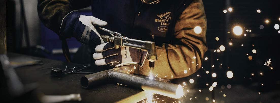 Operario suelda metal