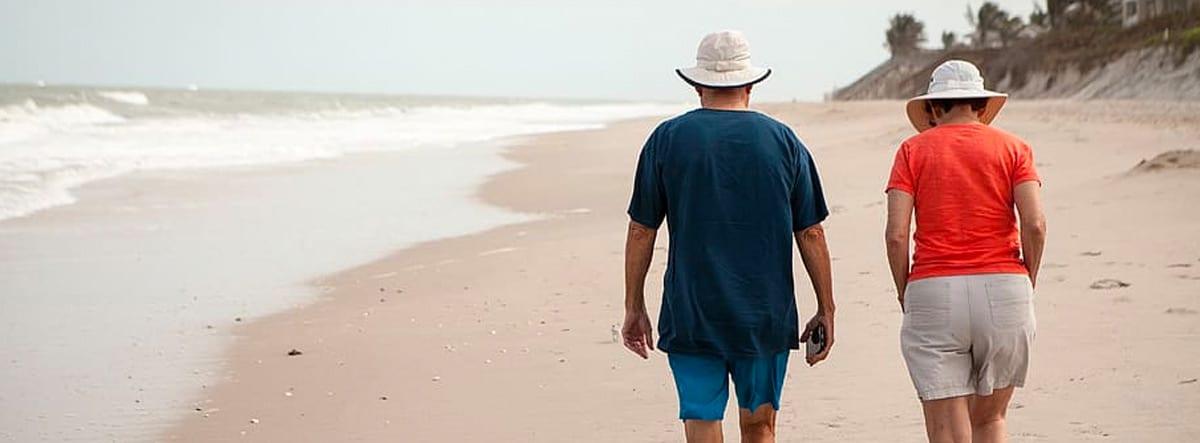 Hombre y mujer mayores paseando por la playa