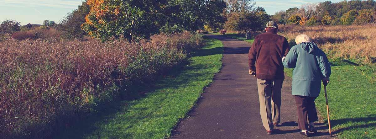 Hombre y mujer mayores con bastón paseando por un camino en el campo