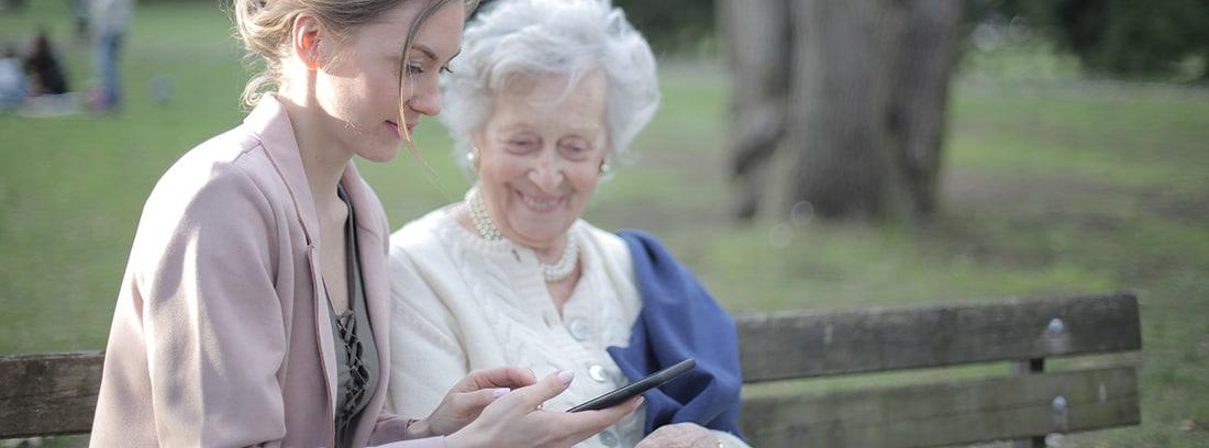 Anciana con mujer joven mirando un smartphone