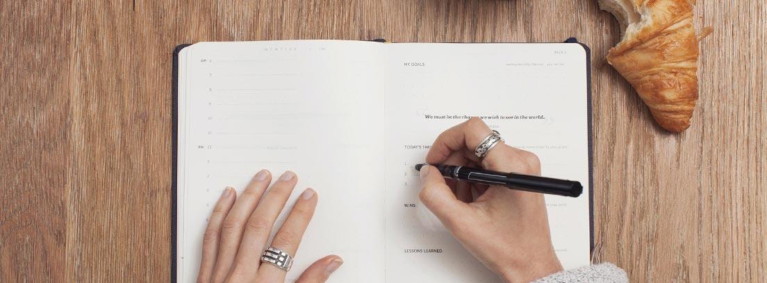 Mujer escribe en una libreta mientras desayuna