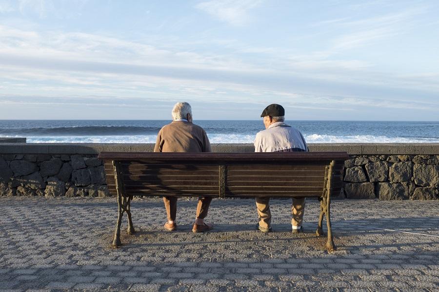 jubilados sentados en un banco frente al mar