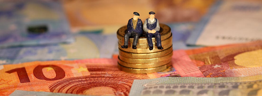 Dos figuras de hombres sobre una columna de monedas y billetes