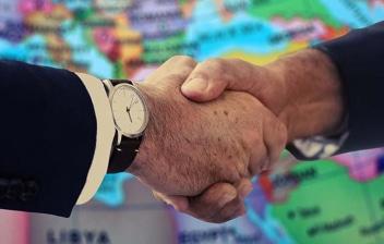 Manos estrechándose delante de un mapa del mundo como metáfora de los acuerdos bilaterales entre dos países