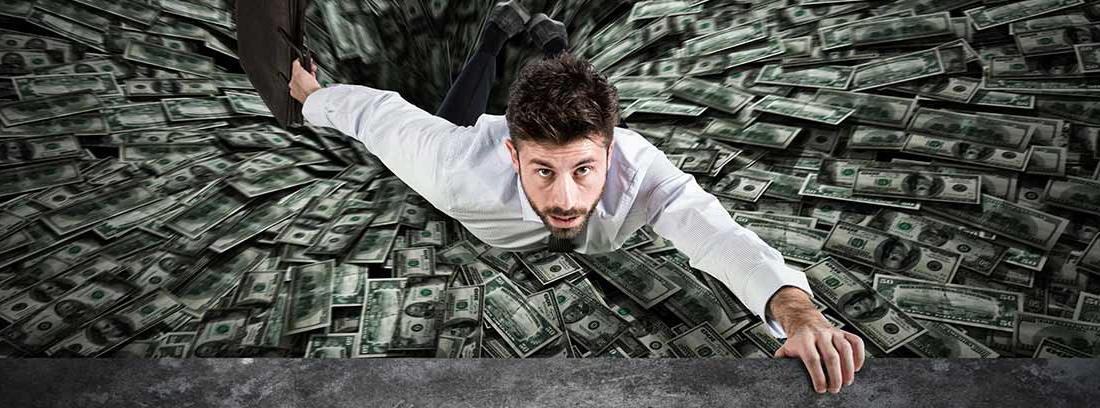 Un hombre intenta emerger de un mar de dólares