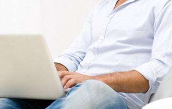 Chico sentado en un sofá con un portátil