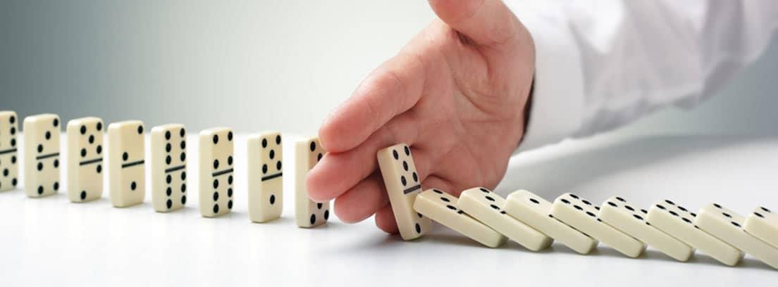 Mano deteniendo la caída de fichas de dominó en fila