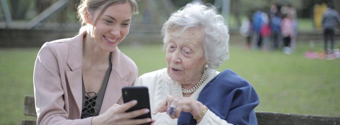 Una anciana observa la pantalla de un smartphone que le enseña una mujer joven