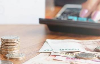 Manos con calculadora junto a monedas y billetes