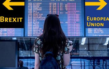"""Mujer de espaldas en un aeropuerto mirando unos carteles que indican """"Brexit"""" y """"European Union"""""""