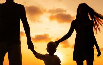 Silueta de un hombre, un niño y una mujer en la playa al atardecer