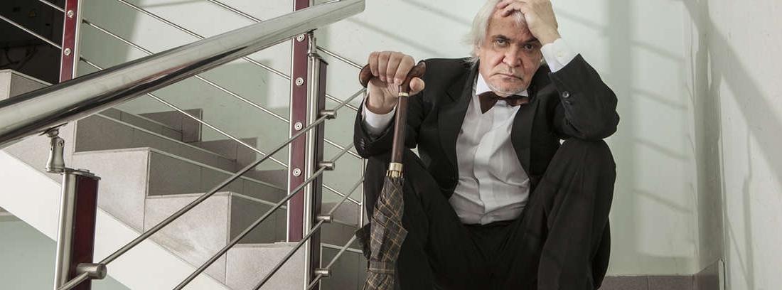 Hombre mayor con gesto apesadumbrado sentado en una escalera