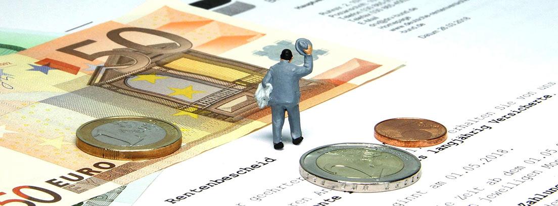 Figura humana sobre unos papeles, billetes y monedas