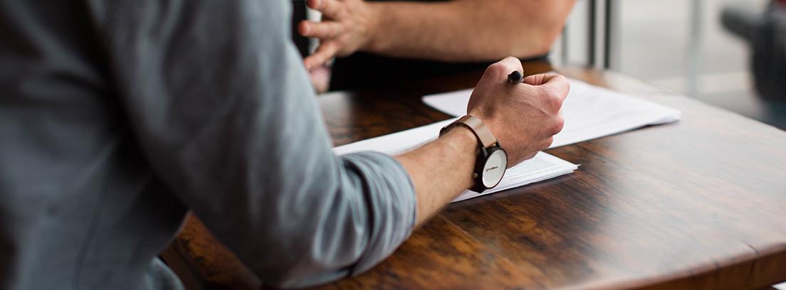 Manos de persona con bolígrafo apuntando sobre papel en mesa de madera