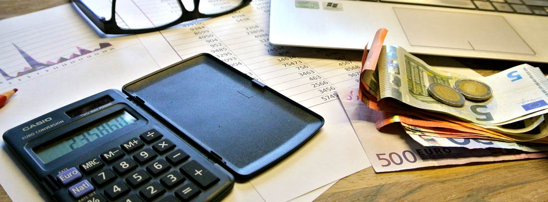 Mesa con calculadora, papeles, billetes y monedas